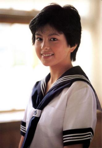 紺色のリボンのセーラー服を着て微笑む若い頃の沢口靖子